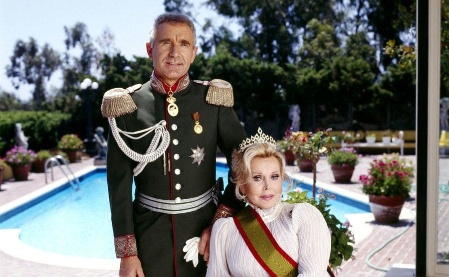 Frederic Prinz von Anhalt and Zsa Zsa Gabor photographed dressed up in front of her back yard pool