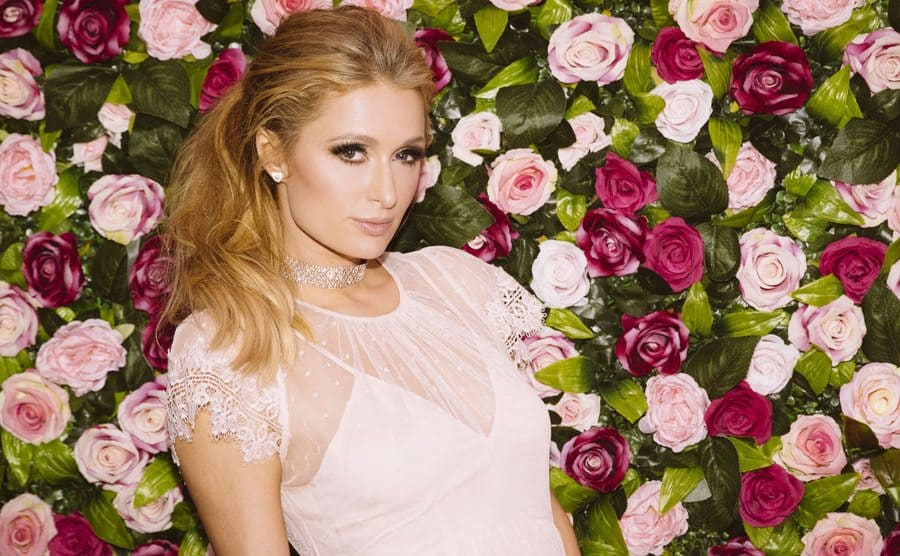 Paris Hilton posing in front of a wall of light and hot pink roses