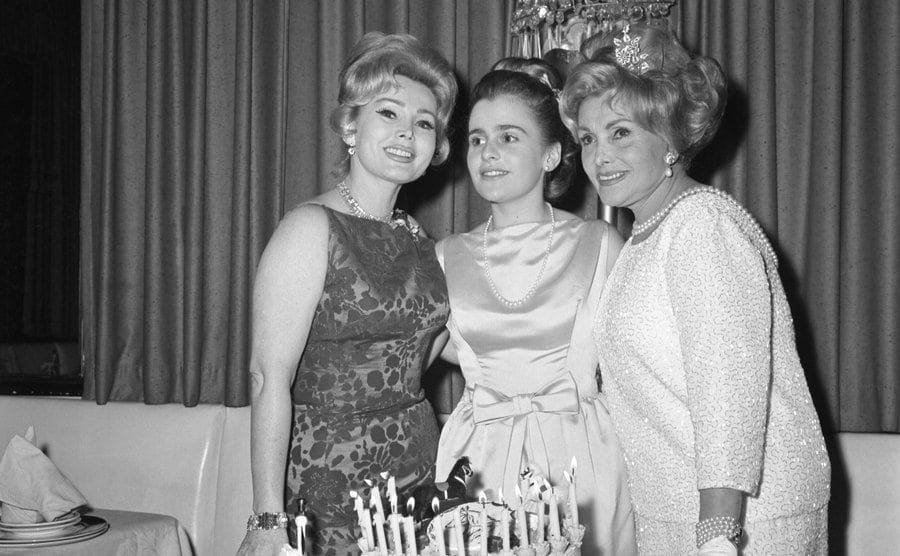 Zsa Zsa Gabor, Francesca Hilton, and Mama Jolie Gabor celebrating Francesca's birthday with a cake in front of them