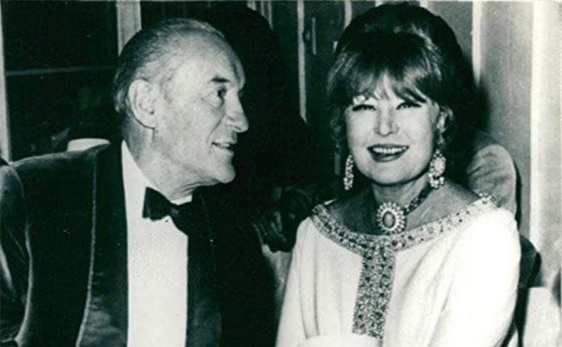George Sanders holding Magda Gabor's hand at a dinner table
