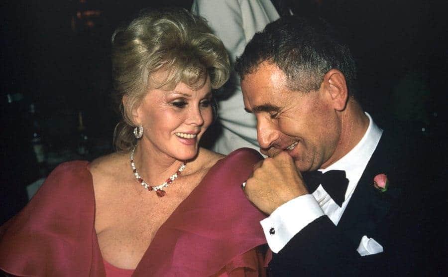 Zsa Zsa Gabor and Frederic Prinz von Anhalt sharing an inside joke at a dinner event in 1989
