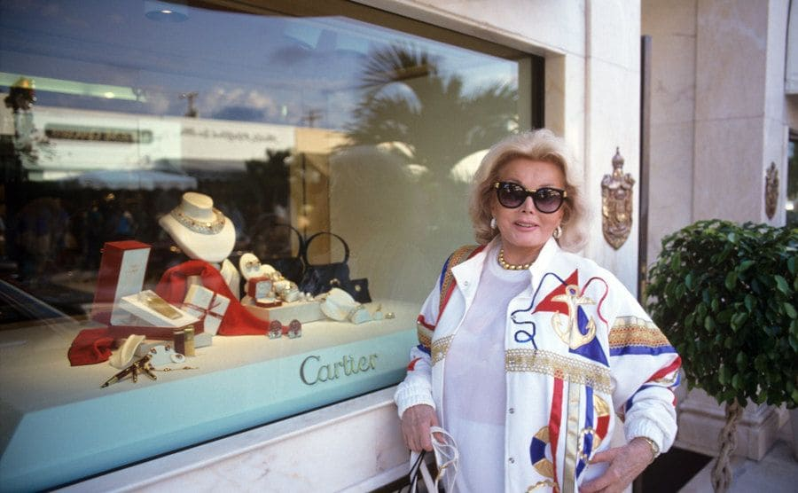 Zsa Zsa Gabor standing in front of a Cartier display window in 1992