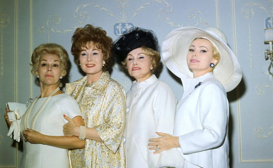 Zsa Zsa Gabor with her two sisters and mother posing in front of a light blue wall