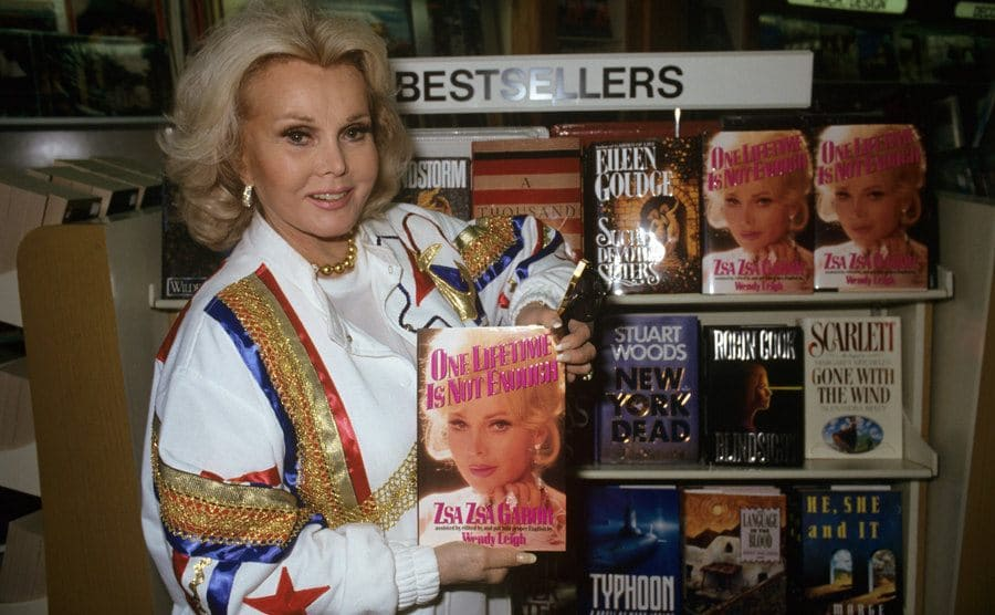 Zsa Zsa Gabor holding her book standing next to a stand labeled 'Bestsellers' at a book store