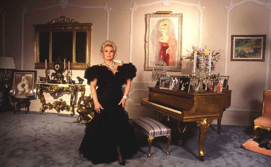Zsa Zsa Gabor standing inside of her home next to a piano filled with photographs