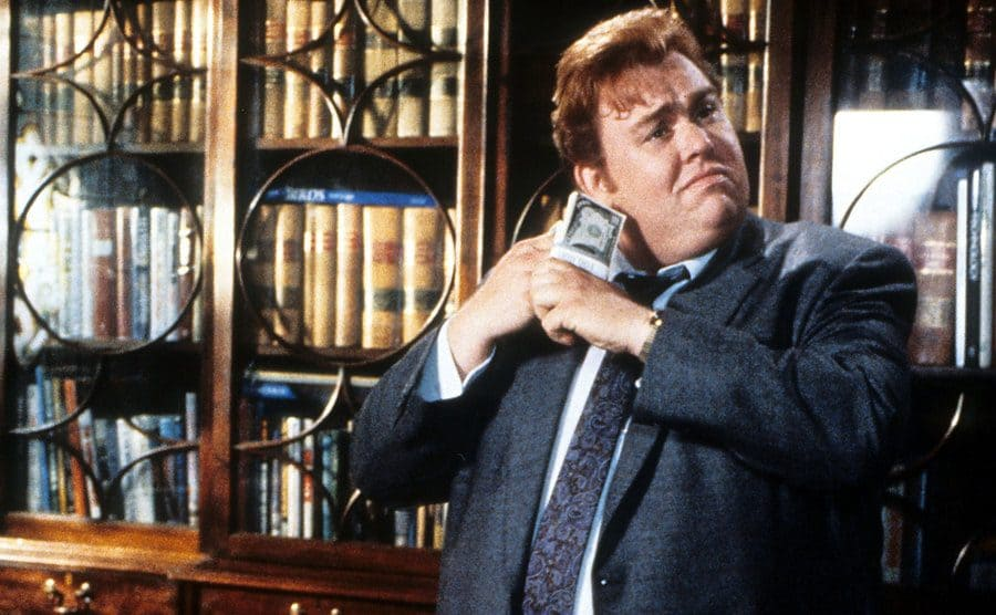 John Candy listening to a wad of cash being fanned out in a scene from Who's Harry Crumb
