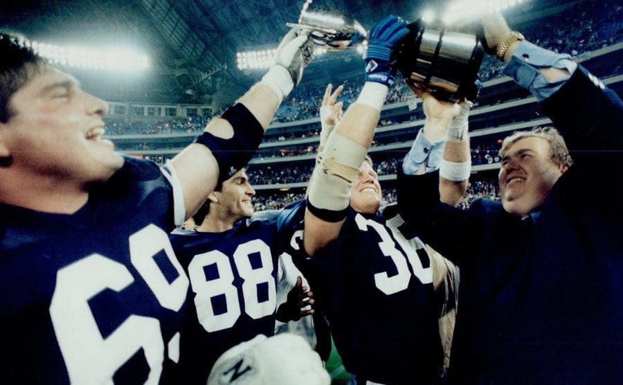 John Candy hoisting up an award with other football players in uniform around him on the field