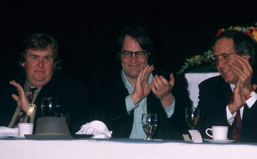 John Candy, Dan Aykroyd, and Chevy Chase clapping sitting at a table with cups of coffee and water