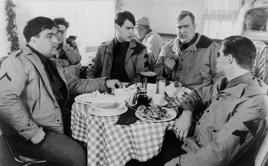 John Candy sitting around a table with Dan Aykroyd, Treat Williams, Walter Olkewicz, and Mickey Rourke in a scene from 1941