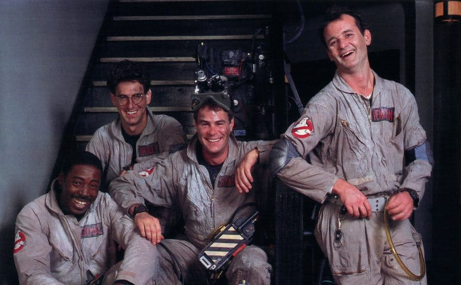 Bill Murray, Ernie Hudson, Dan Aykroyd, and Harold Ramis in their ghostbusters uniforms sitting at the bottom of a set of steps