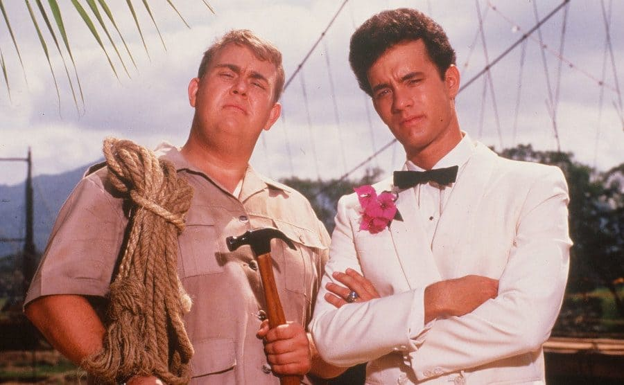 John Candy and Tom Hanks posing together in front of a small body of water in the film Volunteers