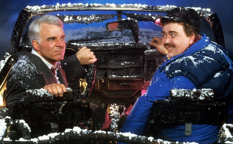 Steve Martin and John Candy sitting in an ash-covered car, Martin looking upset and Candy looking guilty