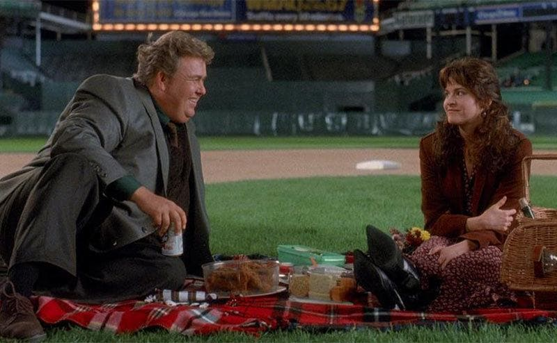 John Candy sitting on a picnic blanket on a date in a scene from Only the Lonely