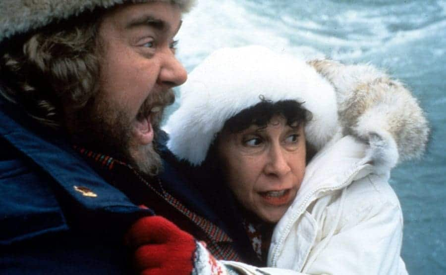 John Candy and Rhea Perlman hugging and looking with fear at something in the distance
