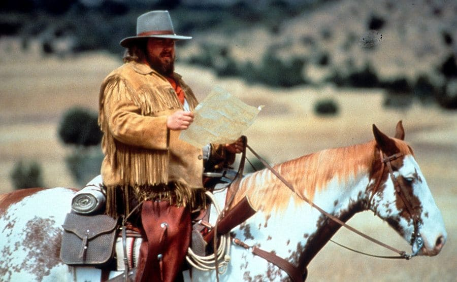 John Candy reading a map while sitting on a horse in a field