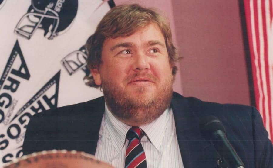 John Candy standing behind a podium with a football showing in the corner of the photograph