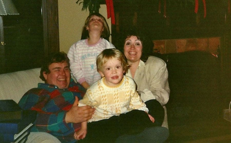 John Candy with his wife and two kids laughing on the couch