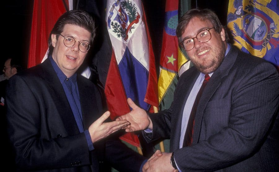 John Hughes and John Candy shaking hands and gesturing towards one another for a photograph