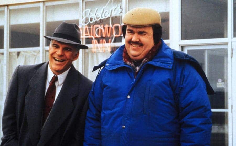 Steve Martin and John Candy laughing outside of an Inn in the film Planes, Trains, and Automobiles
