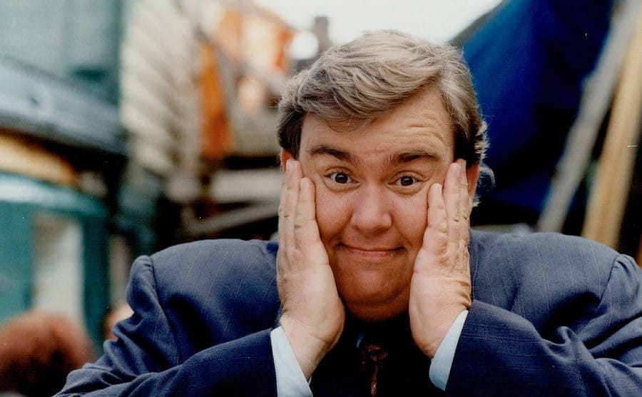 John Candy with his hands on his face