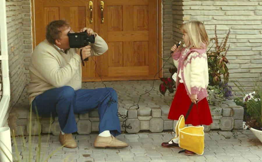 John Candy filming his daughter Jen on the front porch of their home while she talks into a microphone holding a backpack