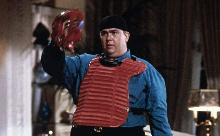 John Candy dressed as a catcher for a baseball game in a scene from a movie