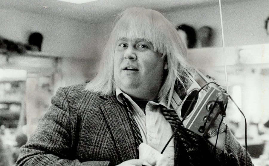 John Candy with a blonde wig on holding an old stereo on his shoulder