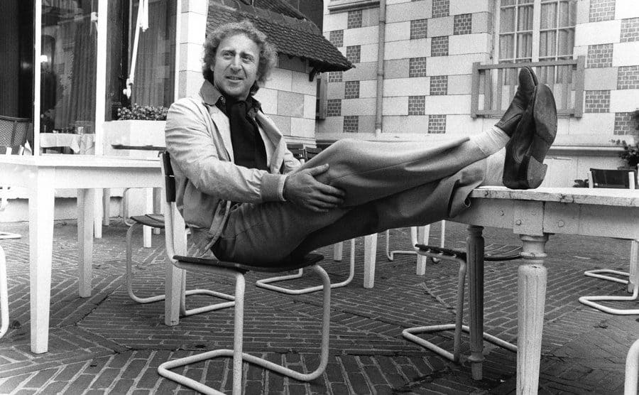 Gene Wilder posing with his feet up on a table