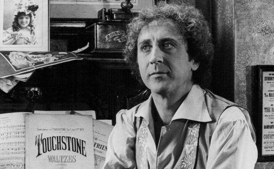 Gene Wilder posing sitting in front of a piano
