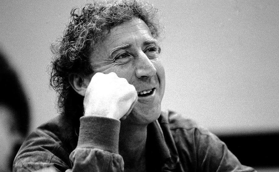 Gene Wilder smiling with his hand on his cheek