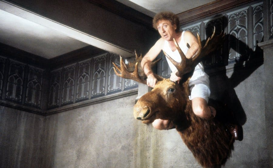 Gene Wilder sitting on top of a moose head mounted on a wall