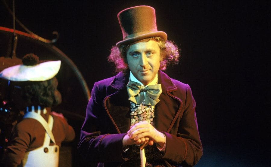 Gene Wilder as Willy Wonka sitting on the edge of the boat