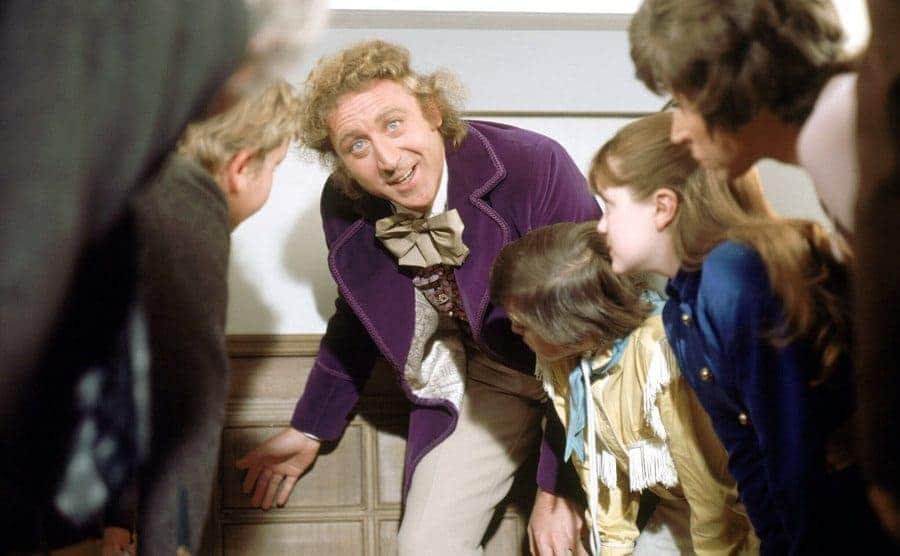 Gene Wilder with the children of Willy Wonka around him about to go through a short door