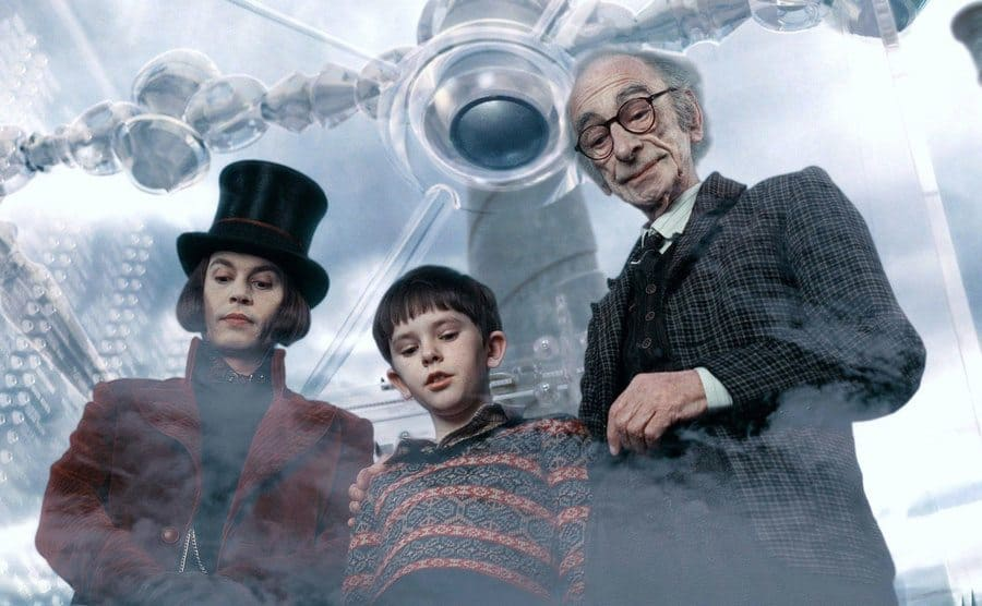 Johnny Depp, Freddie Highmore, and David Kelly looking downward in a scene from Charlie and the Chocolate Factory