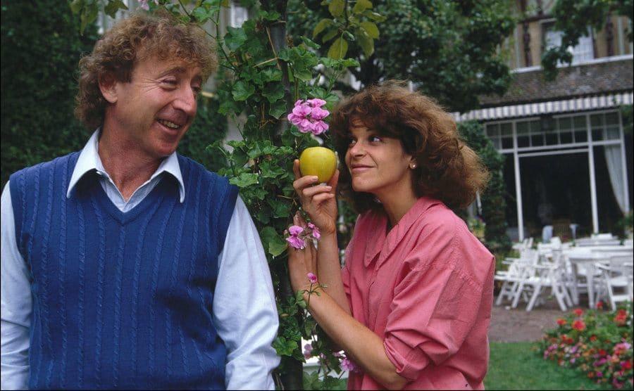 Gene Wilder and Gilda Radner posing next to green leaves holding an apple