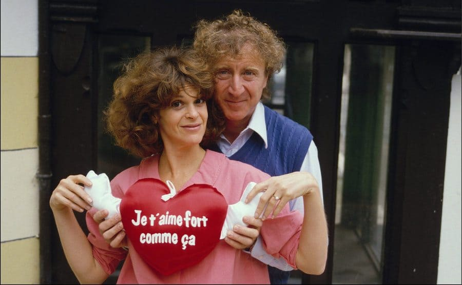 Gene Wilder hugging Gilda from behind while holding a heart pillow