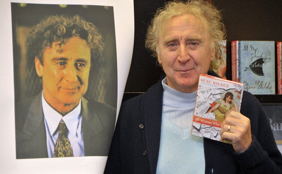 Gene Wilder holding up a copy of his book in front of a photograph of himself