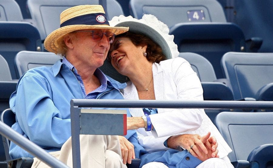 Gene Wilder and Karen Boyer laughing together in the stadium at a tennis match