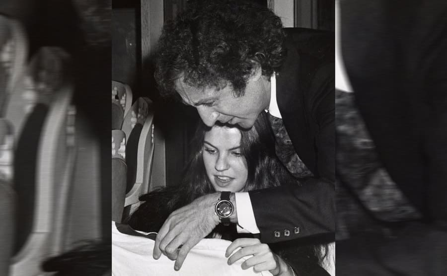 Katherine and Gene Wilder looking at something sitting at a table during an event