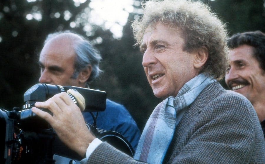 Gene Wilder behind a camera on the set of a movie 1984