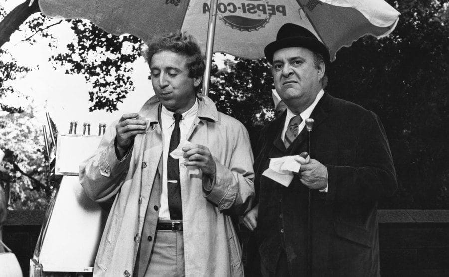 Gene Wilder and Zero Mostel enjoying a hot dog from a vendor on the set of The Producers