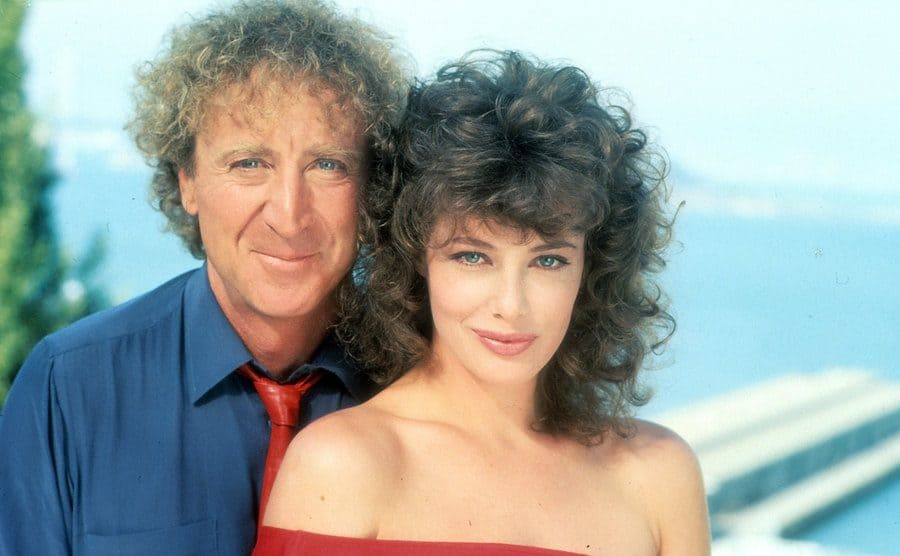 Gene Wilder and Kelly LeBrock in the film 'The Woman in Red' posing in front of an ocean view