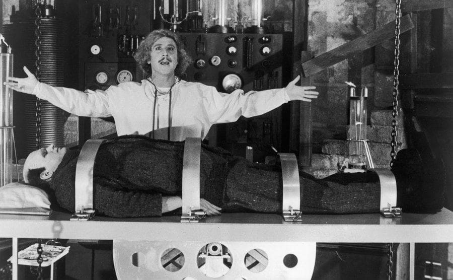 Gene Wilder standing in front of Frankenstein on a surgical table