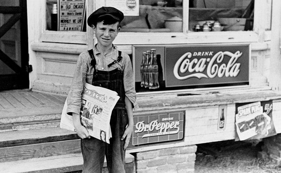 A young farm boy selling a newspaper on the streets.