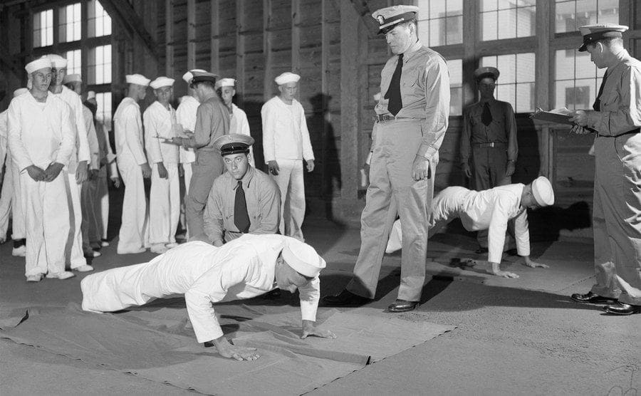 An officer supervising one of his training programs exercises by watching a couple of GOBS doing pushups.