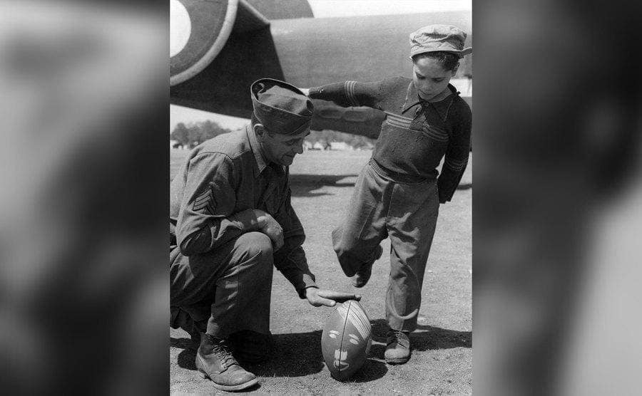 A soldier and child playing American football.