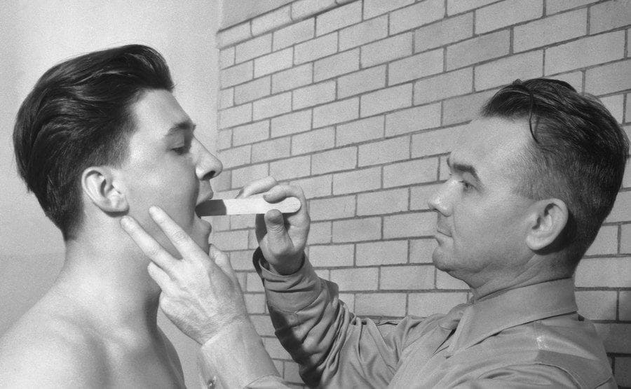 Boy going through motions of enlisting in the Army. Shown here getting his teeth examined by recruiter.