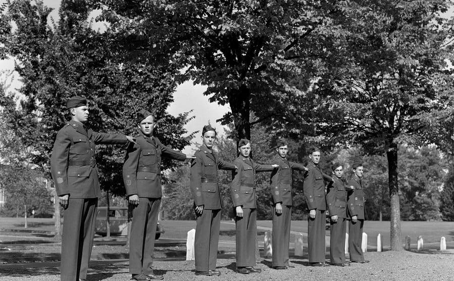 Eight young men standing in formation and in uniform as part of basic training.