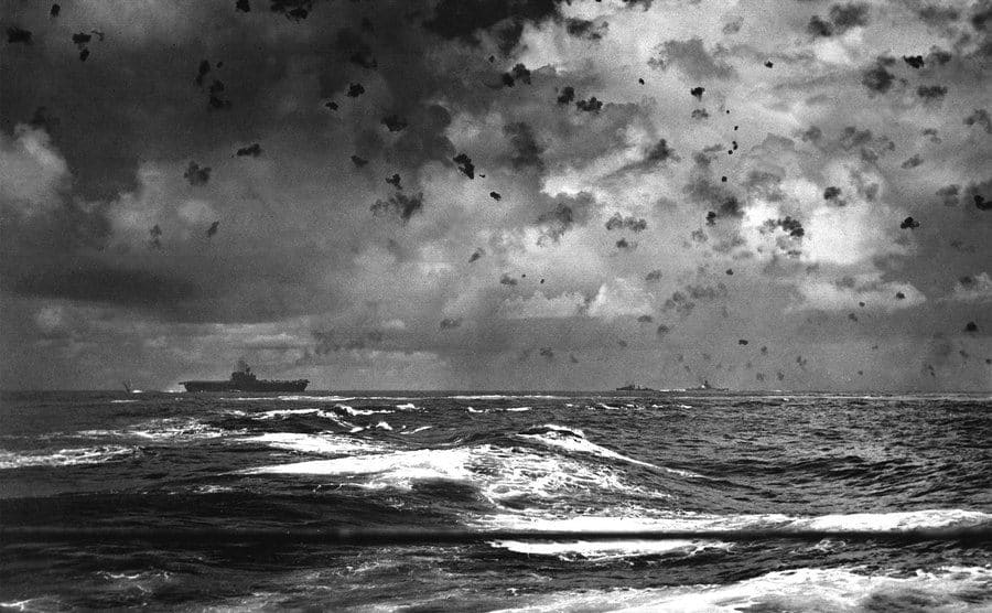 View of Santa Cruz's battle, as the Japanese bomb splashes towards the rear of the American aircraft carrier, clouds of anti-aircraft fire fill the skies above the ships.