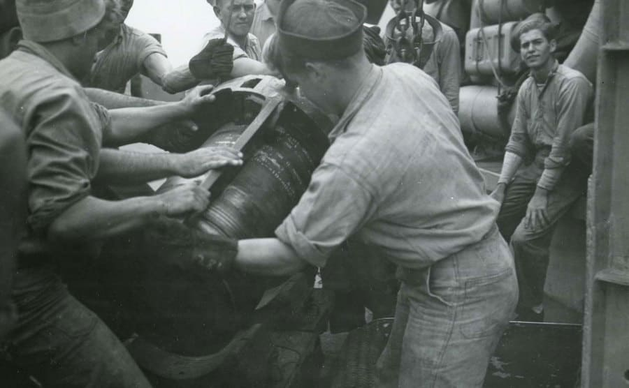 Crew members are loading a 16-inch shell aboard a battleship.